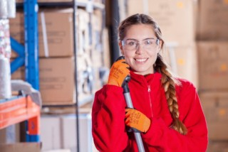 woman in red jacket standing in a warehouse