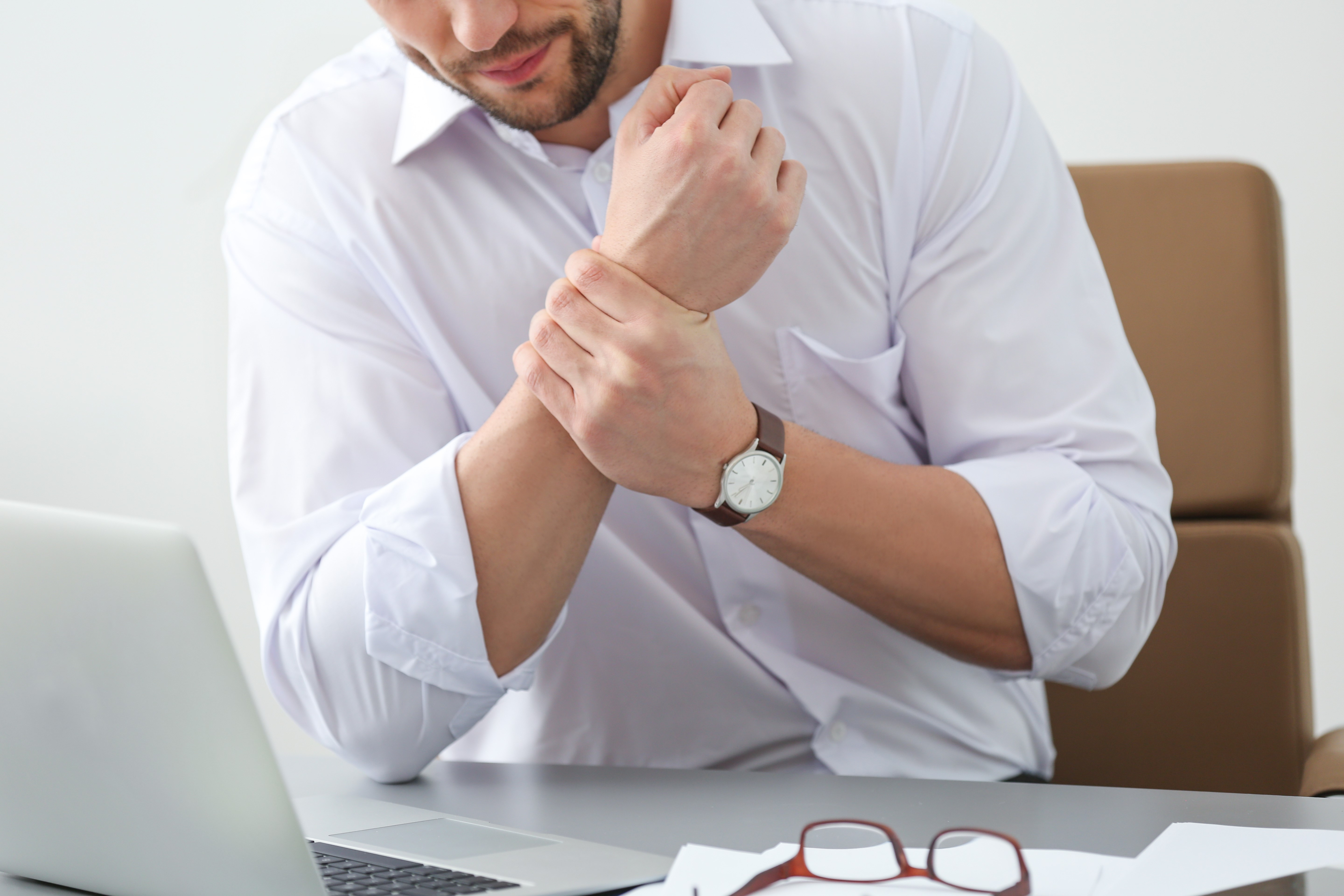man grabbing hurt wrist due to a repetitive stress injury