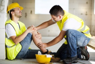 One construction worker helping another with a workplace injury